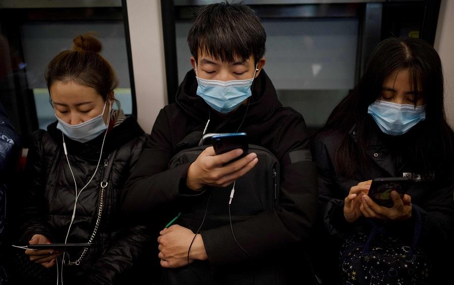 People wearing face masks use their mobile phone on a subway in Beijing on 19 December 2020. (Noel Celis/AFP)