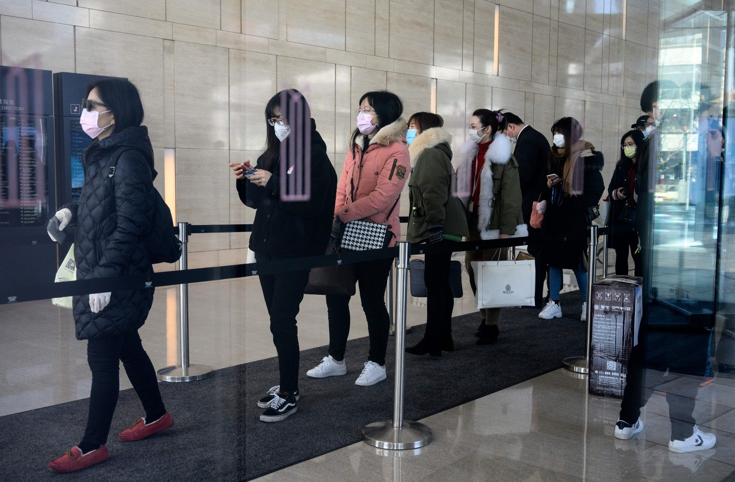 Employees wearing protective face masks queue as they return to work at an office building in Shanghai on 10 February 2020. (Noel Celis/AFP)