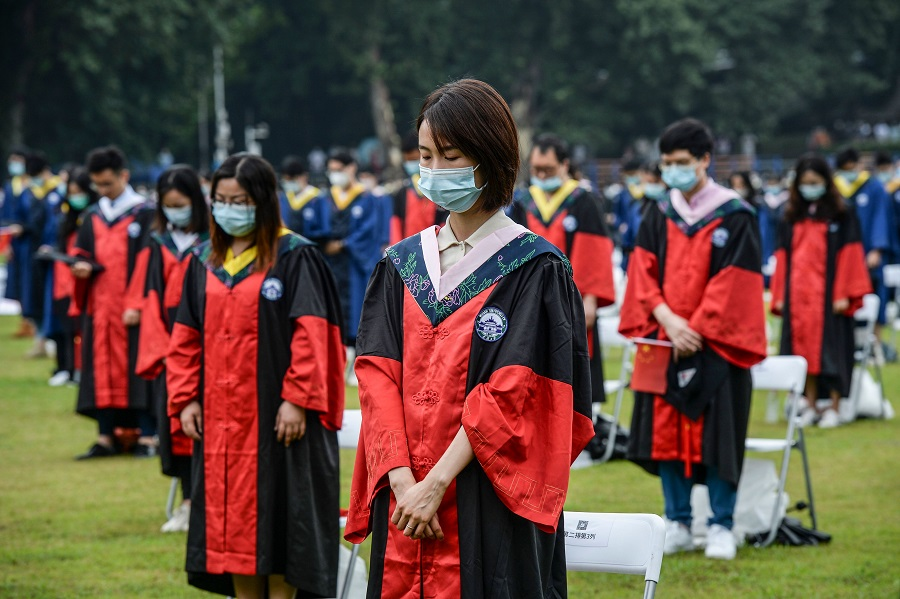 This photo taken on 20 June 2020 shows university graduates standing in silent tribute for victims of the Covid-19 pandemic during their graduation ceremony in Wuhan University in Wuhan, Hubei, China. (STR/AFP)