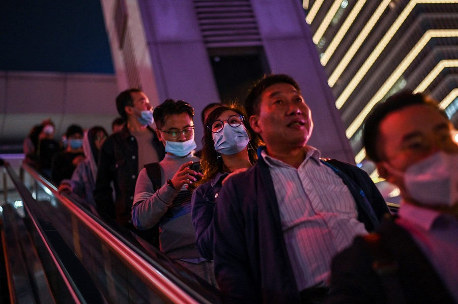 In this picture taken on 25 October 2020, people wearing face masks travel on an escalator in the financial district of Lujiazui in Shanghai, China. (Hector Retamal/AFP)