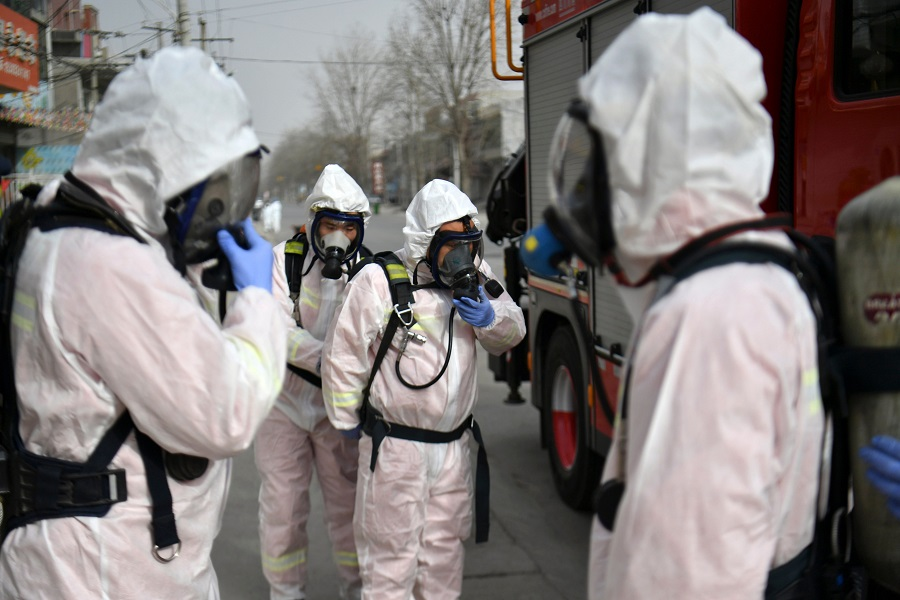 This photo taken on 15 January 2021 shows people in protective suits preparing to spray disinfectant on a street at Gaocheng district, which was declared a high-risk area for Covid-19 in Shijiazhuang, in China's Hebei province. (STR/CNS/AFP)