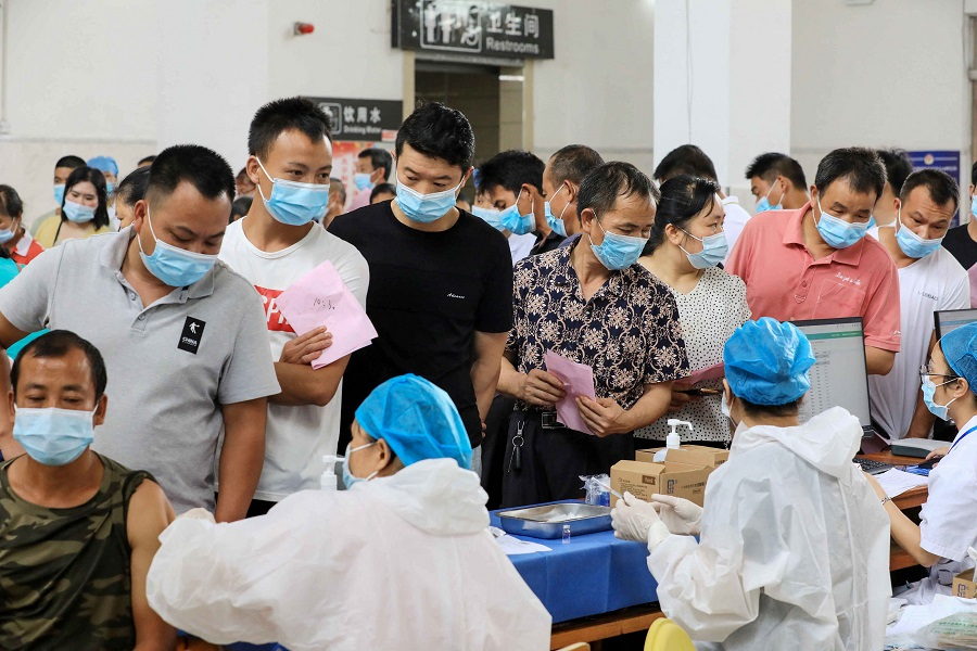 This photo taken on 3 June 2021 shows residents queueing to receive the Sinovac Covid-19 coronavirus vaccine in Rong'an, Guangxi, China. (STR/AFP)