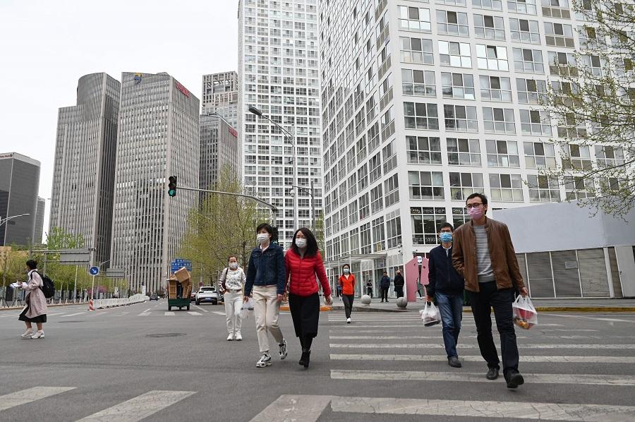 Pedestrians wearing face masks cross a street in Beijing on 8 April 2020. (Wang Zhao/AFP)