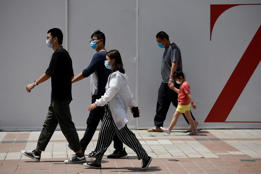 People wearing face masks amid the Covid-19 pandemic walk along a street in Beijing on 20 May 2020. (Wang Zhao/AFP)