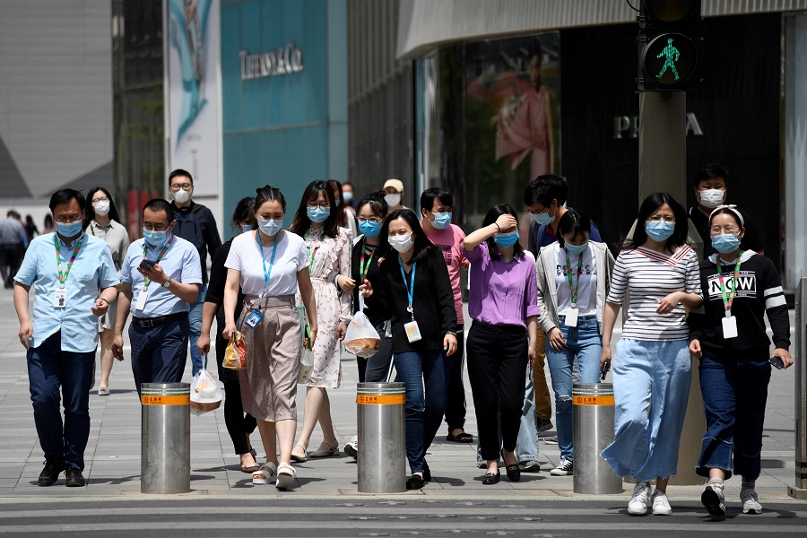 People wearing face masks amid the Covid-19 pandemic cross a street in Beijing on 20 May 2020. (Wang Zhao/AFP)