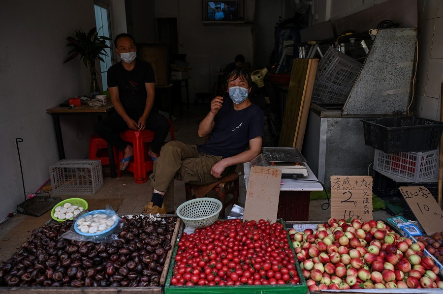 Vendors wearing face masks wait for customers in a market in Wuhan, China, on 18 May 2020. (Hector Retamal/AFP)