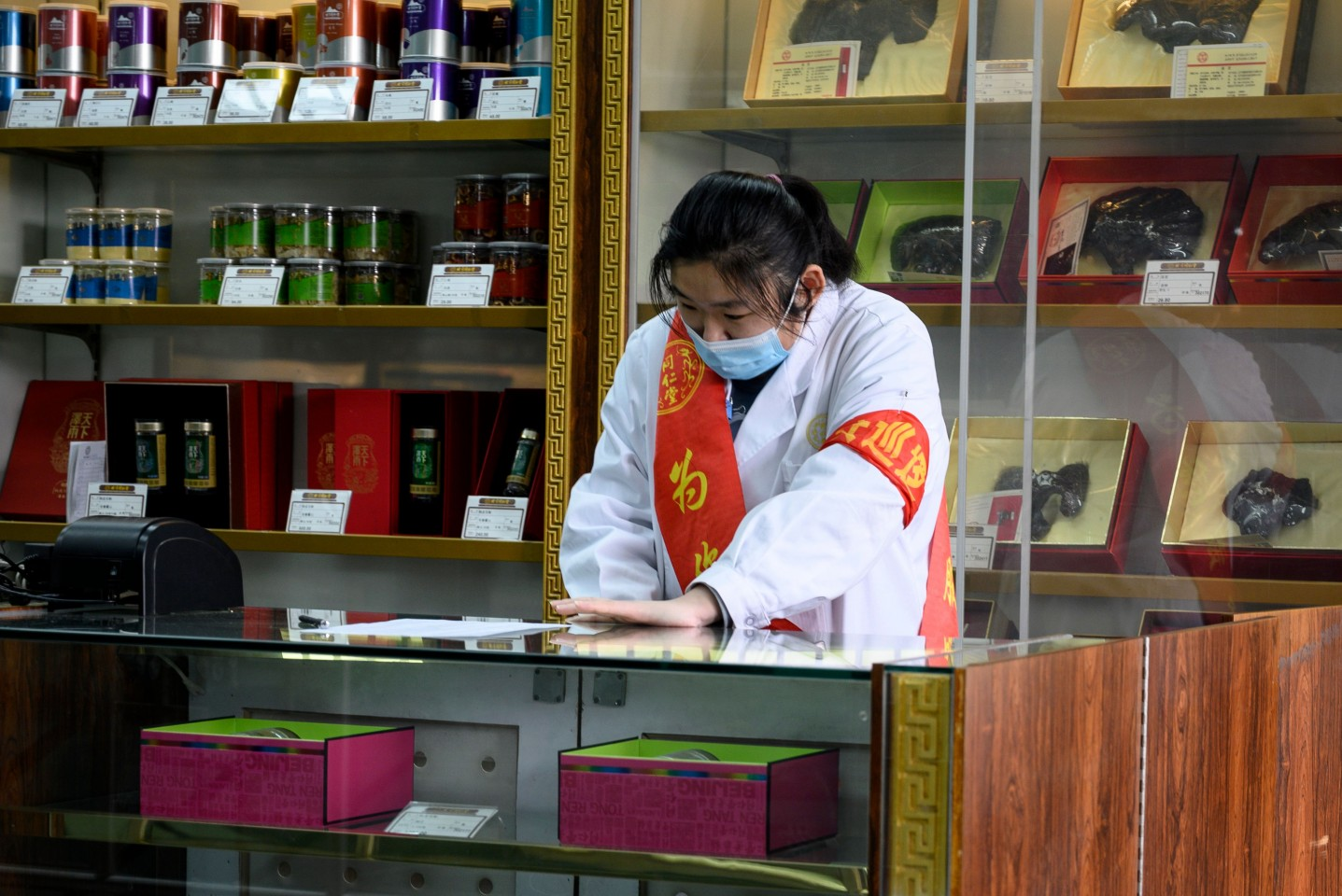 This photo taken on 1 February 2020 shows an employee wearing a protective face mask at a traditional Chinese medicine store in Beijing. (Noel Celis/AFP)
