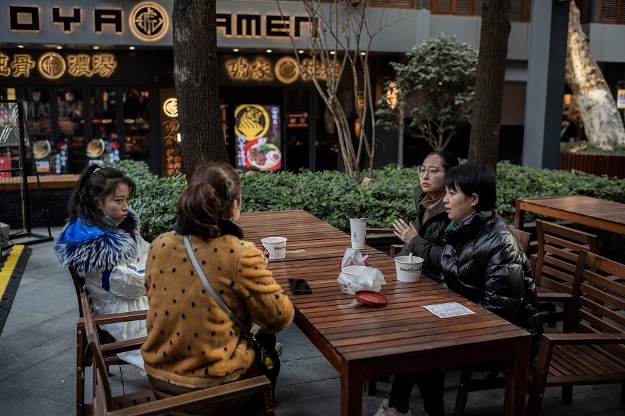 People chat as they have lunch at a food court in Wuhan on 13 January 2021. (Nicolas Asfouri/AFP)