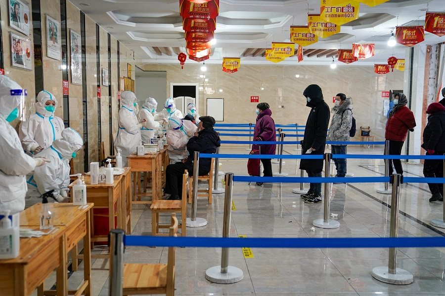 A medical worker takes a swab sample from a man as people queue to get tests for the Covid-19 coronavirus at an office building in Harbin, Heilongjiang province, China, on 14 January 2021. (STR/AFP)