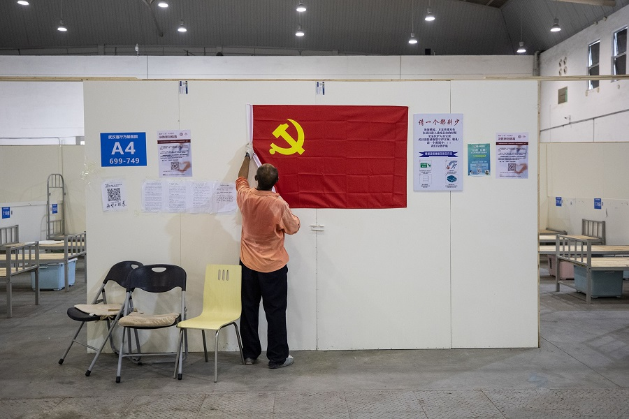 A worker removes a Communist Party flag as workers demolish installations at Wuhan's makeshift hospital built to treat patients infected by the Covid-19 coronavirus in China's Hubei province on 29 July 2020. (STR/AFP)