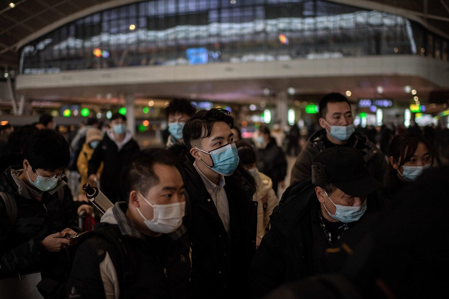 People wearing face masks wait to board a train at the main railway station in Wuhan, China, on 10 January 2021. (Nicolas Asfouri/AFP)