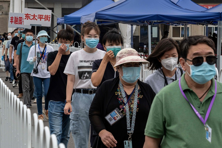 People wearing face masks gather at an outdoor area during a mass testing for the Covid-19 coronavirus at the Jinrong Street testing site in Beijing on 24 June 2020. (Nicolas Asfouri/AFP)