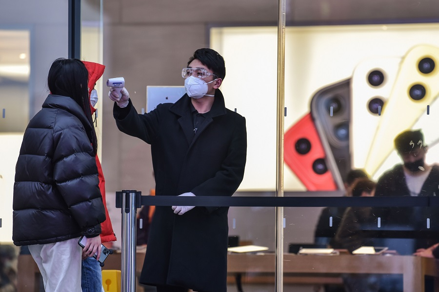 A security guard checks the temperature of customers at the entrance of an Apple store in Shanghai on 28 February 2020. (Hector Retamal/AFP)