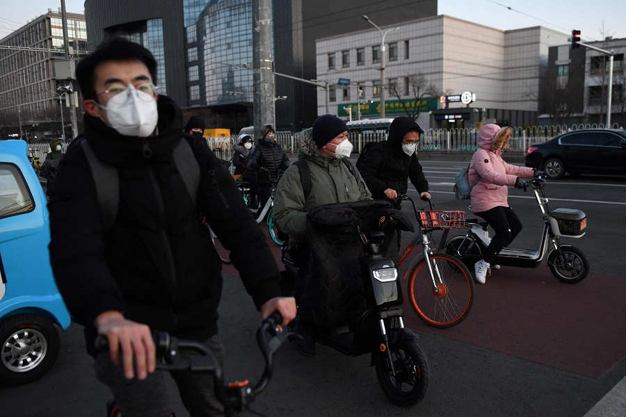 People wear face masks as a preventive measure against the Covid-19 coronavirus as they wait to cross a street in Beijing on 3 March 2020. (Greg Baker/AFP)
