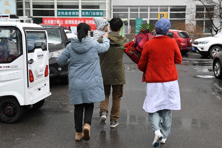A nurse (right) accompanies a one-year-old boy and his parents as they leave after their recovery from the Covid-19 coronavirus, at the Youan Hospital in Beijing on 14 February 2020. (Greg Baker/AFP)