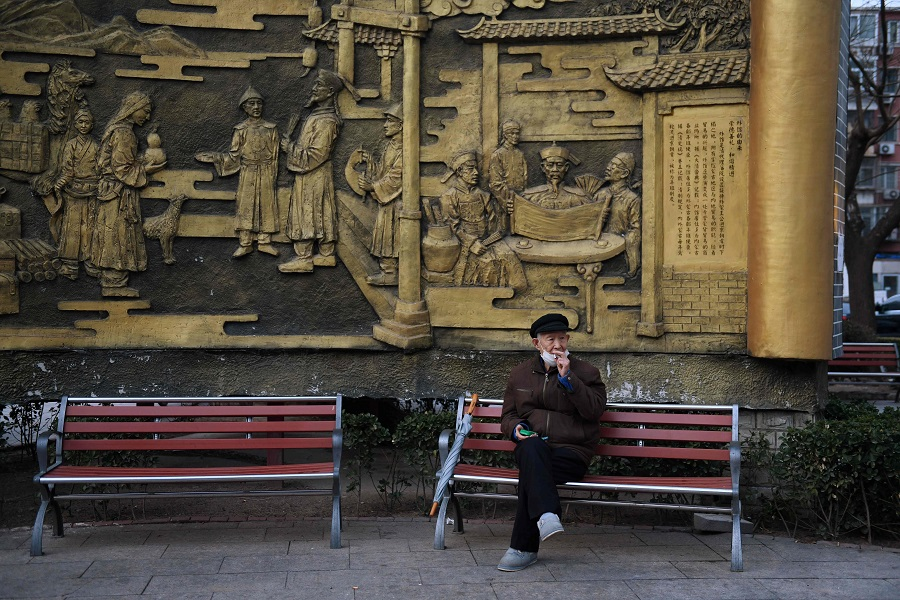 A man lowers his mask to smoke a cigarette in Beijing on 9 March 2020. (Greg Baker/AFP)