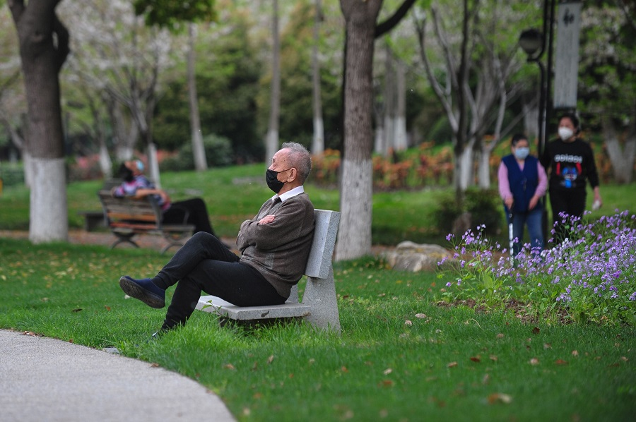 A man sits on a bench at a park in Wuhan, China, on 26 March 2020. (STR/AFP)