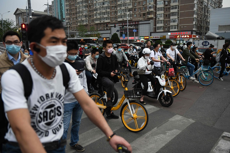 People wear face masks as a precaution against the Covid-19 coronavirus as they wait to cross a road during rush hour in Beijing on 15 May 2020. (Greg Baker/AFP)