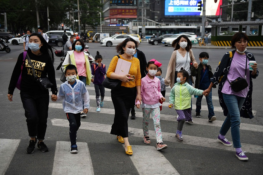 A group of women and children wear face masks as a precaution against the Covid-19 coronavirus as they cross a road in Beijing on 15 May 2020. (Greg Baker/AFP)