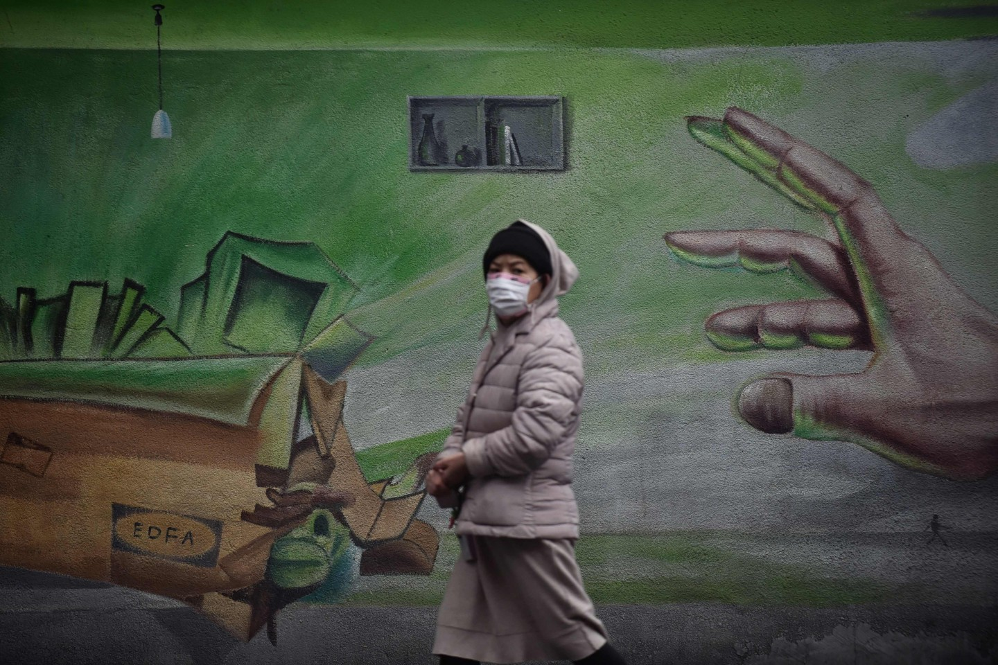 This photo taken on 28 February 2020 shows a resident walking past a mural in Wuhan. (STR/AFP)