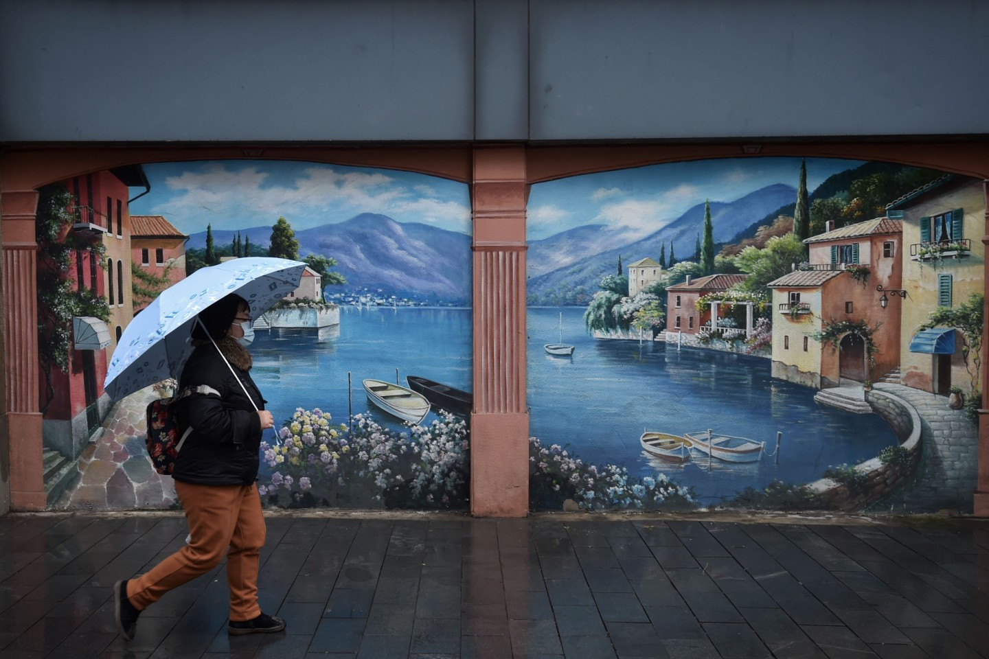 This photo taken on 28 February 2020 shows a resident walking past a mural in Wuhan, in China's central Hubei province. (STR/AFP)