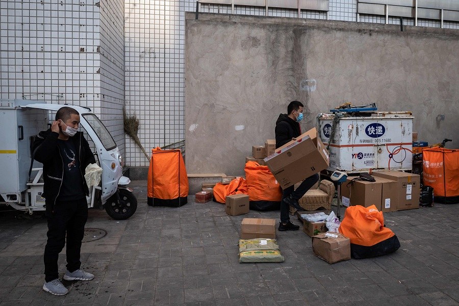 Delivery workers wearing face masks amid concerns over the Covid-19 coronavirus sort out their delivery items on a street in Beijing on 22 April 2020. (Nicolas Asfouri/AFP)