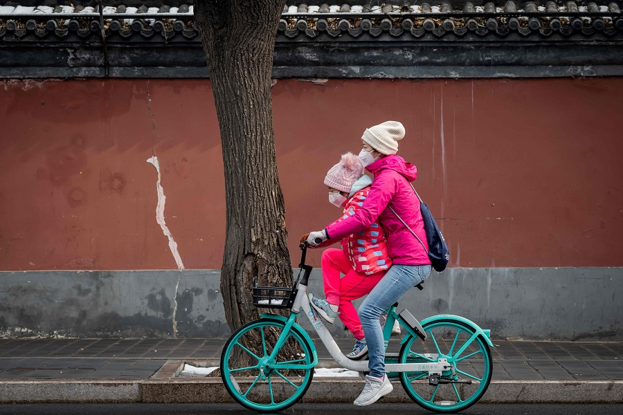 A woman and a girl wearing protective masks to prevent the spread of Covid-19 ride on a bicycle in Beijing on 2 February 2020. (Nicolas Asfouri/AFP)