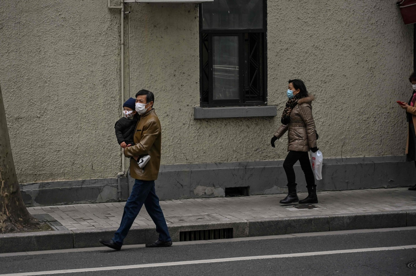 People wearing face masks walk on a street in Shanghai on 3 March 2020. (Hector Retamal/AFP)