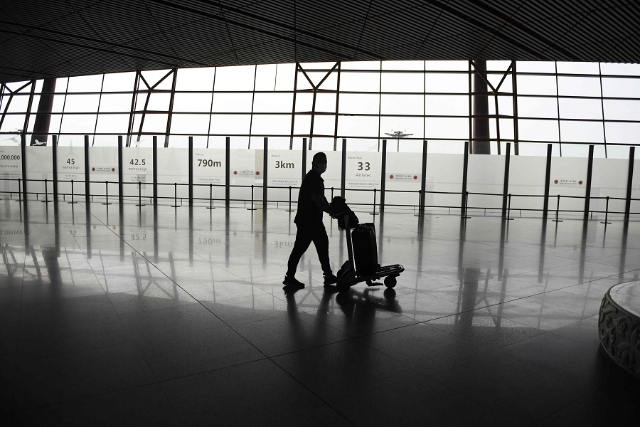 A lone passenger walks through the airport in Beijing on 18 June 2020. (Greg Baker/AFP)
