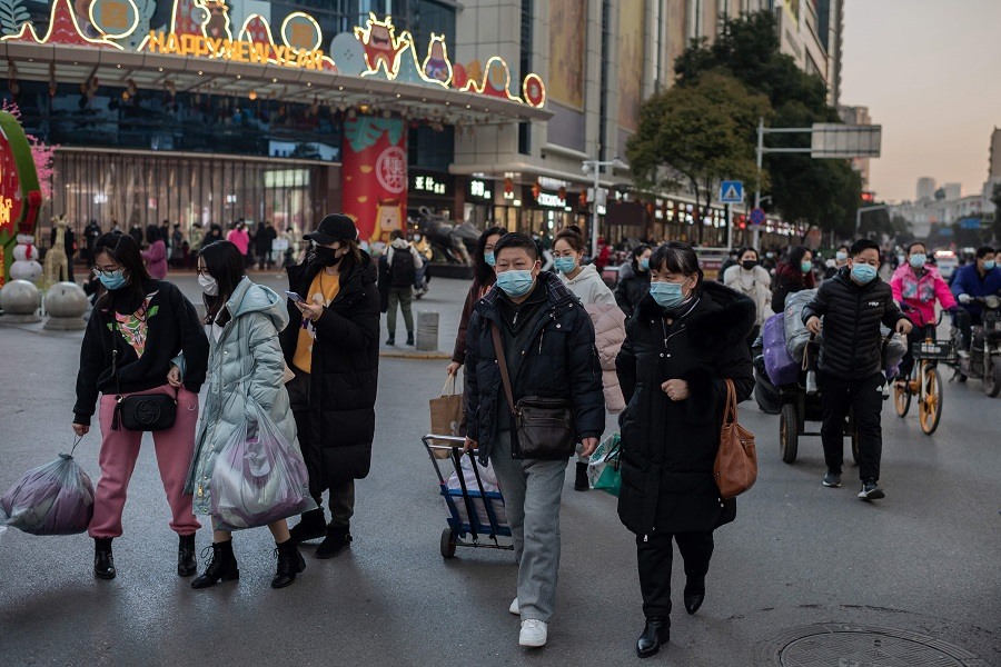 People wearing face masks walk outside of a shopping mall complex during rush hour in Wuhan on 13 January 2021. (Nicolas Asfouri/AFP)