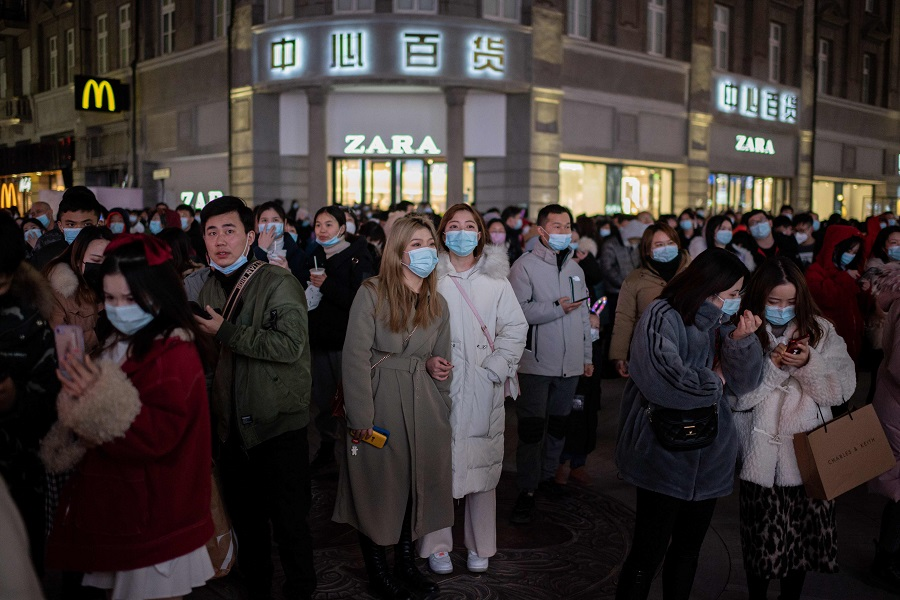 People wearing face masks stand around a giant 3D screen on Jianghan street in Wuhan on 10 January 202. (Nicolas Asfouri/AFP)