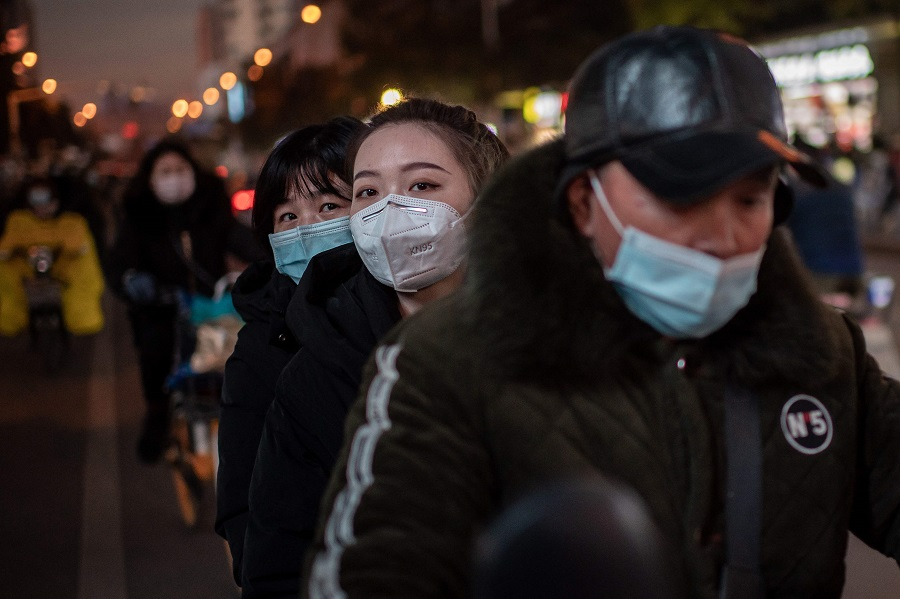 Women wearing face masks ride on a motorcycle during rush hour in Wuhan, Hubei, China, on 13 January 2021. (Nicolas Asfouri/AFP)