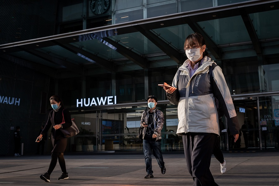 People wearing a wearing face masks as a preventive measure against the Covid-19 coronavirus walk outside a shopping mall past a Huawei shop in Beijing on 1 April 2020. (Nicolas Asfouri/AFP)