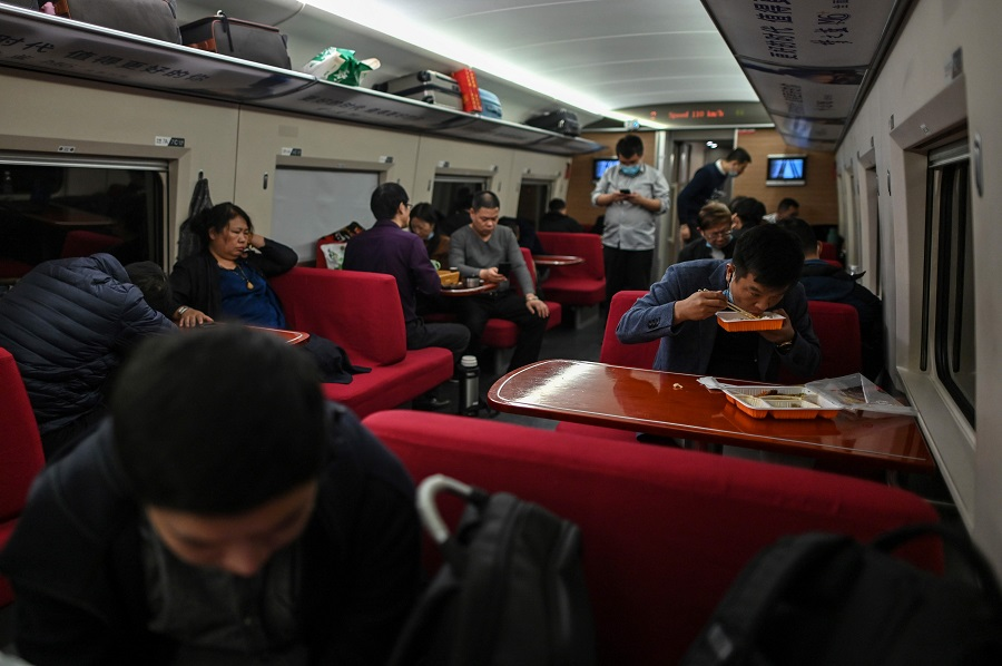 Passengers travel in a train heading to Wuhan, in Shanghai on 19 November 2020. (Hector Retamal/AFP)
