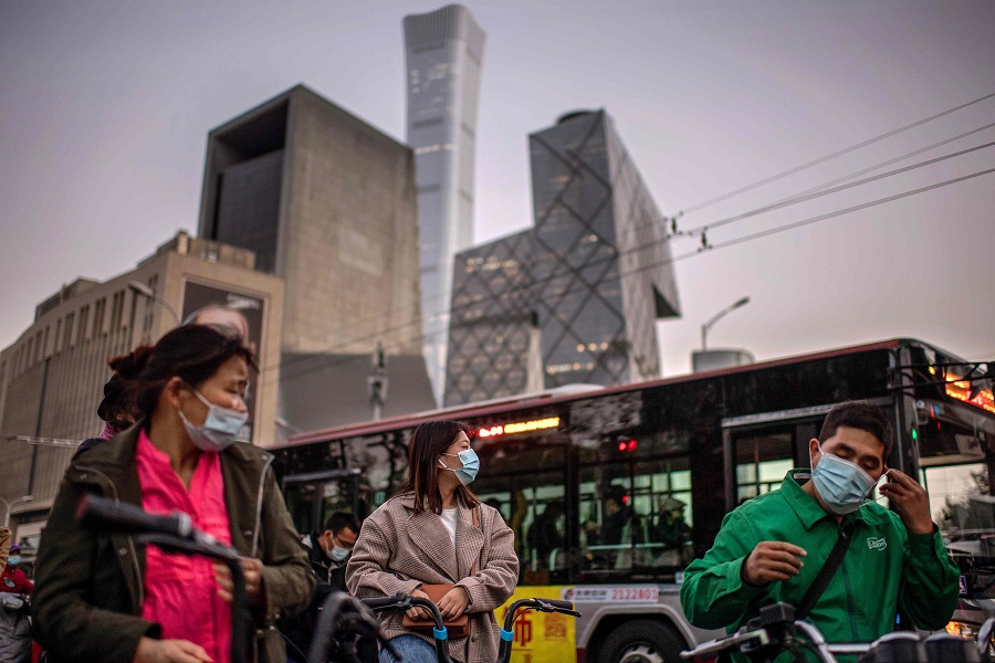 People wearing face masks wait to cross a street during rush hour in Beijing on 21 October 2020. (Nicolas Asfouri/AFP)