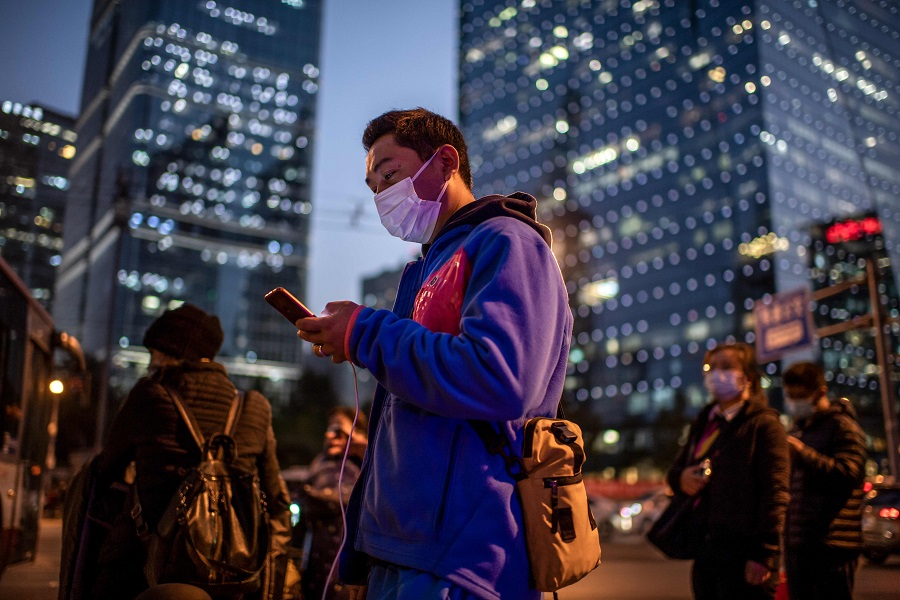 A man (centre) wearing a face mask looks at his mobile phone as he waits to cross a street during rush hour in Beijing on 21 October 2020. (Nicolas Asfouri/AFP)