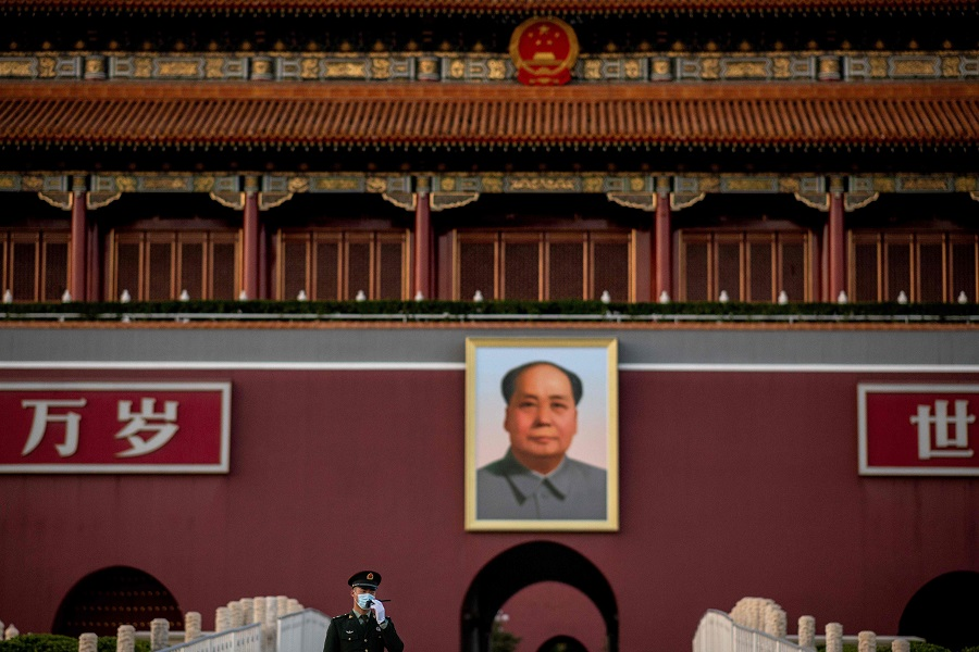 A paramilitary police officer wearing a face mask talks on his radio transmitter as he stands in front of the portrait of late communist leader Mao Zedong at Tiananmen Gate in Beijing on 13 October 2020. (Nicolas Asfouri/AFP)