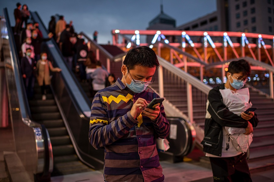 Mask-clad people are seen using their phones outside a shopping mall in Beijing on 11 October 2020. (Nicolas Asfouri/AFP)