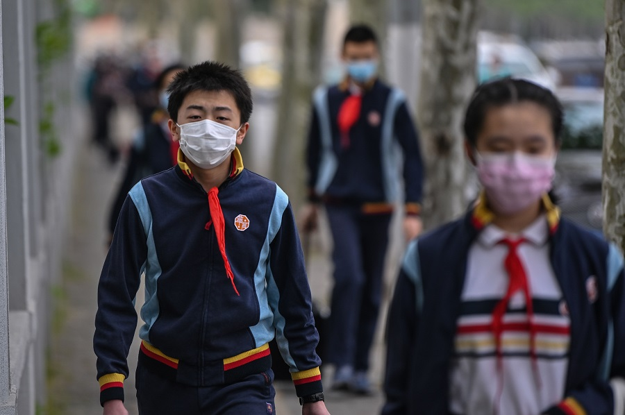 Students wearing face masks arrive at the Huayu Middle School in Shanghai on 27 April 2020. (Hector Retamal/AFP)