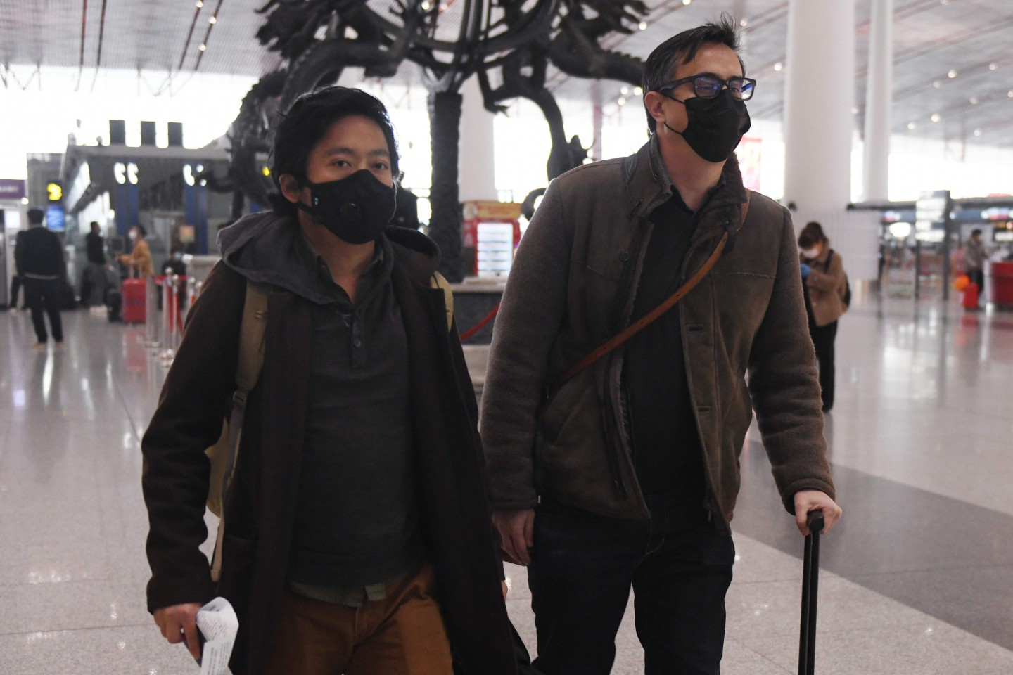Wall Street Journal reporters Josh Chin (right) and Philip Wen walk through Beijing Capital Airport before their departure on 24 February 2020. (Greg Baker/AFP)