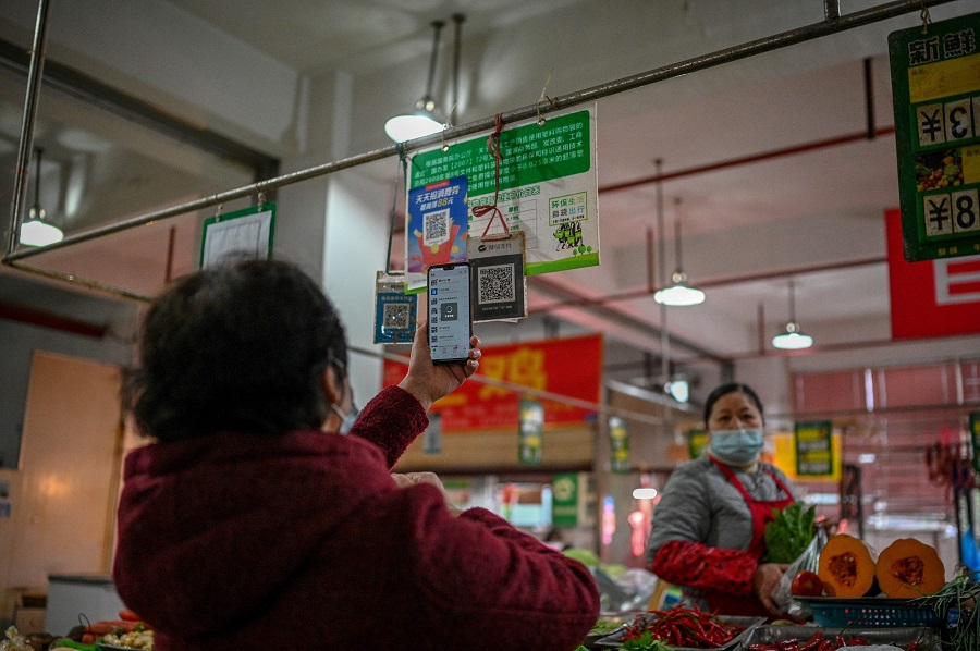 This photo taken on 30 November 2020 shows a woman (left) using her mobile phone to pay for produce at a market in Chengdu, Sichuan province, China. (Noel Celis/AFP)