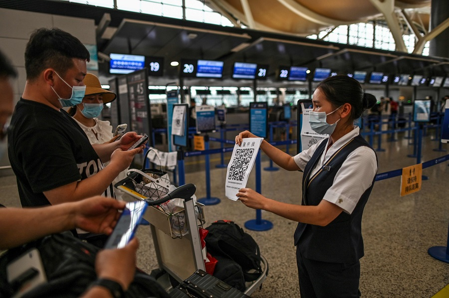 Passengers wearing face masks check their health code with a sheet held by an aiport staff (right) before the counter area in Pudong International Airport in Shanghai, on 11 June 2020. (Hector Retamal/AFP)