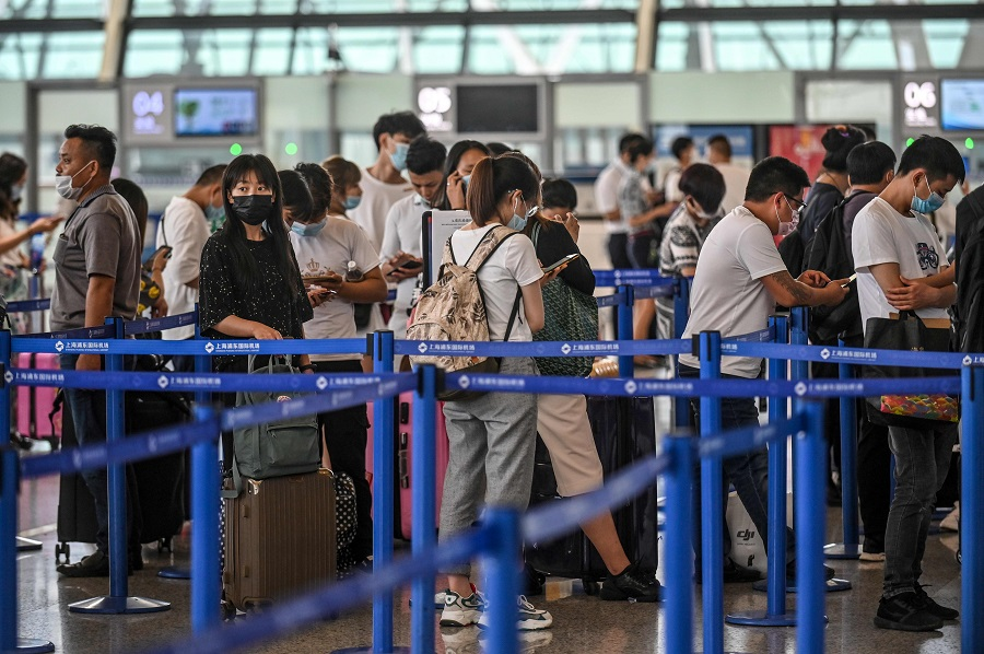 Passengers wait in line at the counter area following preventive procedures against the Covid-19 coronavirus in Pudong International Airport in Shanghai on 11 June 2020. (Hector Retamal/AFP)