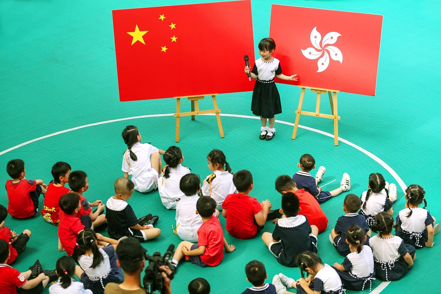 Over in Shenzhen, a child introduces the Hong Kong flag to her classmates at a kindergarten, ahead of Hong Kong's handover anniversary on July 1. (Photo by STR / AFP)