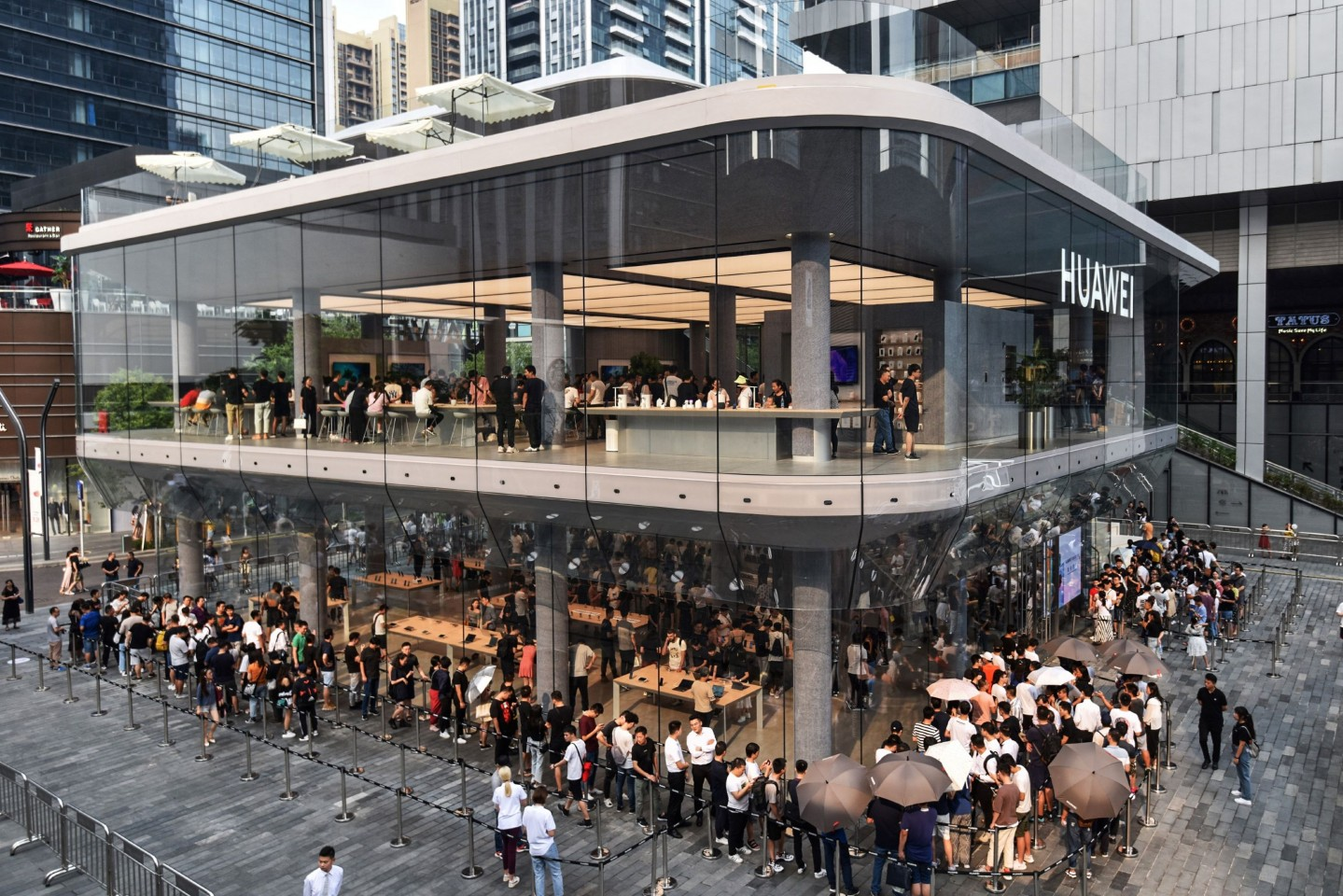 This photo taken on September 28, 2019 shows people queueing outside a newly-opened Huawei flagship store in Shenzhen in China's southern Guangdong province. (Photo by STR / AFP) / China OUT