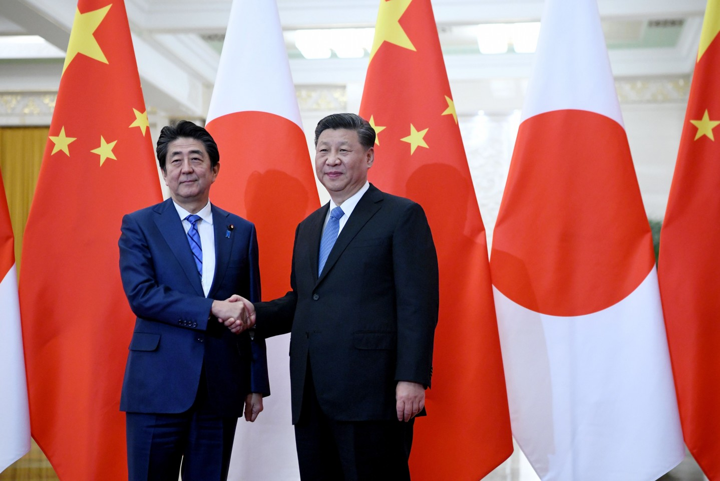 Japan's Prime Minister Shinzo Abe (left) shakes hand with China's President Xi Jinping at the Great Hall of the People in Beijing on December 23, 2019. (Noel Celis/POOL/AFP)