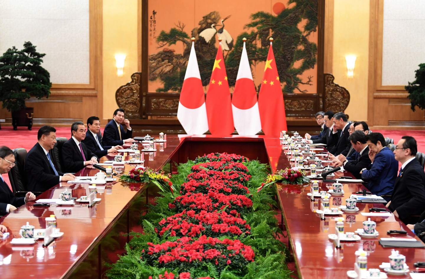 Japan's Prime Minister Shinzo Abe (second, right) talks to China's President Xi Jinping (second, left) during a meeting at the Great Hall of the People in Beijing on 23 December 2019. Xi is expected to visit Japan later this year. (Noel Celis/POOL/AFP)