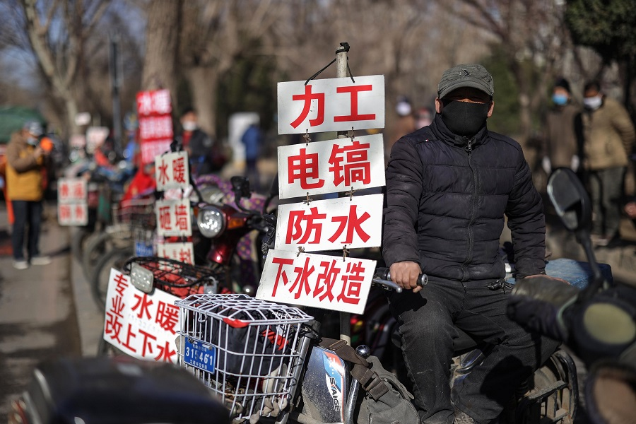 A day labourer wearing a face mask sits next to a sign advertising his skills as he waits to get hired for renovation works in Shenyang, Liaoning province on 27 March 2020. (STR/AFP)