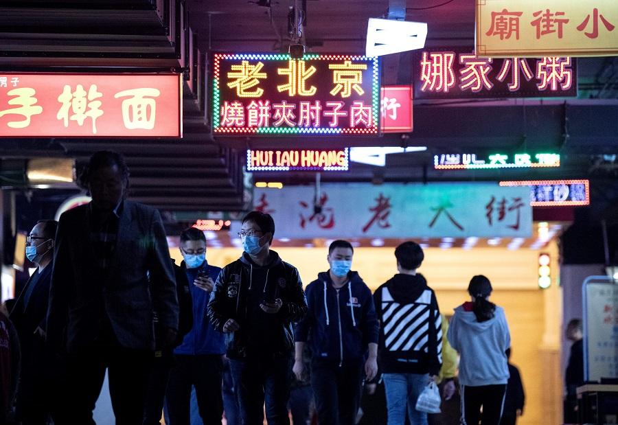 People wearing face masks arrive at a food court during lunch break in Beijing on 14 October 2020. (Noel Celis/AFP)