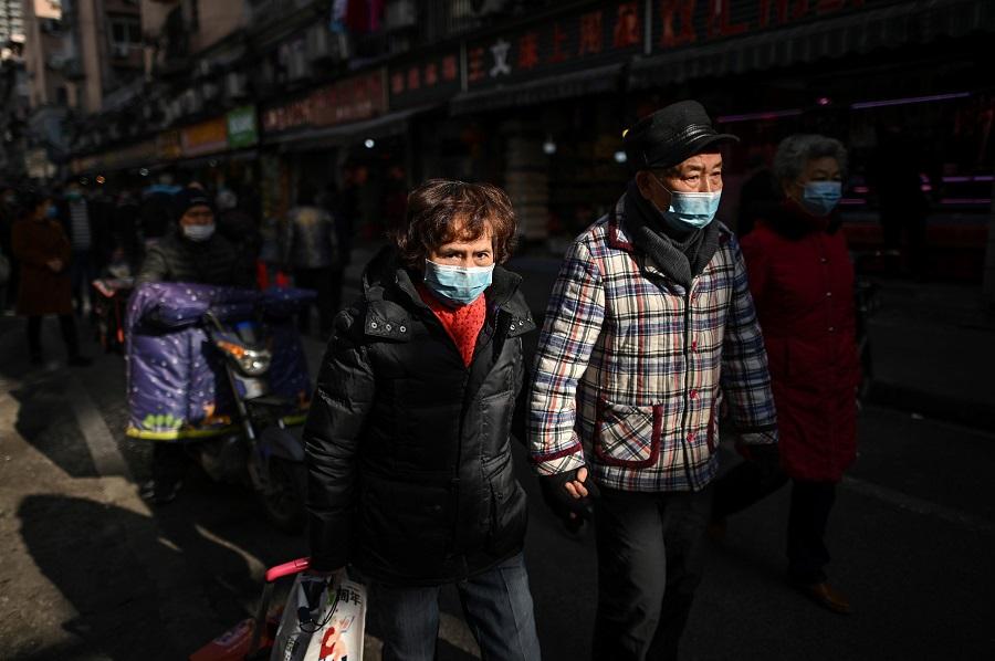 People walk along a street near a market in Wuhan, Hubei province, China, on 19 January 2021. (Hector Retamal/AFP)